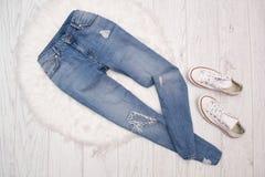 Blues-jean en lambeaux et espadrilles blanches sur la fourrure blanche concept à la mode Photos stock