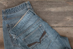 Blues-jean sur un fond en bois brun Images libres de droits