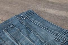 Blues-jean sur un fond en bois brun Image libre de droits