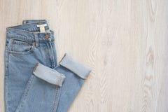 Blues-jean sur un fond en bois Configuration plate de regard dénommé femelle Vue supérieure Concept d'achats Équipements de mode images libres de droits