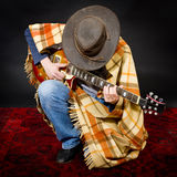 Blues rock. Parody with a manin shabby clothes playing the guitar Royalty Free Stock Image