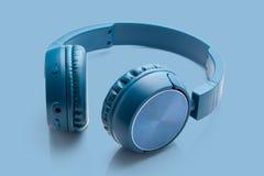 Bluetooth blue headphone on blue background stock image