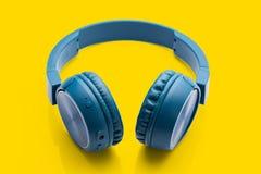 Bluetooth blue headphone on yellow background royalty free stock photo