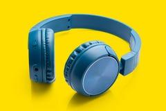 Bluetooth blue headphone on yellow stock image