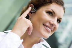 Bluetooth desgastando da mulher de negócios Fotos de Stock Royalty Free