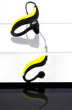 Bluetooth Earphones. Yellow and black Bluetooth earphones on an acrylic box with a black bottom Royalty Free Stock Photo