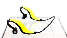 Bluetooth Earphones. Yellow and black bluetooth earphones on an acrylic box on a white background Royalty Free Stock Photo