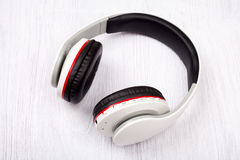 Bluetooth headphones on white wood background Stock Images