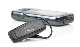 A bluetooth headset. And mobile cell phone on white background Stock Image