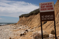 Bluff Erosion Warning. An Erosion sign warning about the dangers ahead. The sign is in the focus point and then it slowly gets slightly out of focus half way Royalty Free Stock Photo