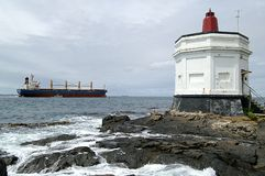 Bluff Lighthouse. Lighthouse, Bluff, New Zealand with container ship being guided out of the harbor Stock Image