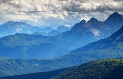 Bluish mist and dark clouds over forested ridges Dolomiti Italy. Glowing blue mist and low dark storm clouds above sunlit green conifer forests, limestone ridges Royalty Free Stock Image