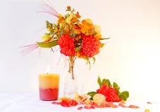 Blume, die mit einer brennenden Kerze vereinbart Lizenzfreies Stockfoto