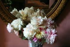 Blumen am atique Spiegel Stockbild