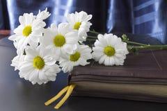 Blumen auf einer Bibel in der Ledergrenze Stockbild