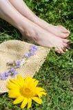 Blumen auf hellgelbem Papierhut und ein Paar Beine Stockfotografie