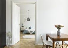 Blumen auf Holztisch im weißen flachen Innenraum mit Lampe über b lizenzfreies stockbild