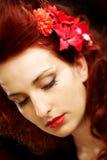 Blumen in auffallendem rotem Haar Lizenzfreie Stockbilder
