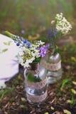 Blumen in den Flaschen im Wald Lizenzfreie Stockfotos