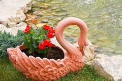 Blumen in einem Schwan-Vase nahe bei einem kleinen See lizenzfreie stockfotografie