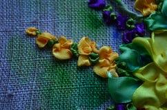 Blumen gestickt mit Farbsatinb?ndern auf dem Gewebe lizenzfreie stockbilder