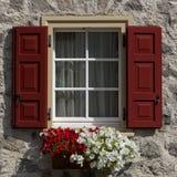 Blumen im Fenster mit offenen hölzernen Fensterläden Stockbild