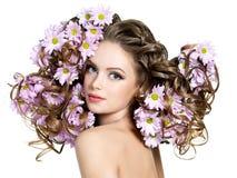 Blumen im langen Haar der reizvollen Frau lizenzfreie stockfotos