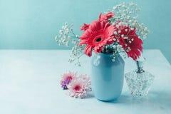 Blumen im Vase mit Frauenparfüm über blauem Hintergrund stockbilder