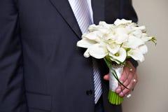 Blumen Kala in der Hand des Bräutigams Stockbilder