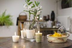 Blumen, Kerzen und gesunde Snäcke auf der Schönheitssalontabelle Stockbild