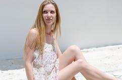 Blumen-Kleiderhaltung der Mode blonde tragende unter hellem Sonnenschein Stockfotografie