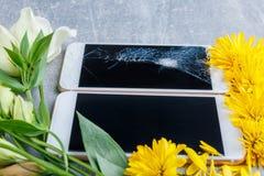 Blumen liegen herum bei zwei Handys, einer von ihnen mit einem defekten Schirm Stockfoto
