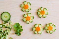 Blumen mit geschnittener frischer Gurke für Dekoration Stockfotografie