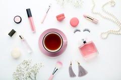 Blumen mit Tasse Tee und Kosmetik stockfotos