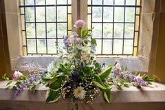 Blumen nahe einem Kirchenfenster stockbilder