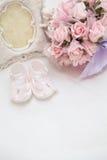 Blumen, photoframe und die Sandalen der Kinder auf dem Bett Stockfoto