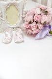 Blumen, photoframe und die Sandalen der Kinder auf dem Bett Lizenzfreies Stockfoto