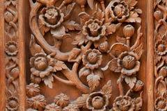 Blumen schnitzten auf einem hölzernen Brett der alten Tür Stockfoto