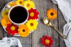 Blumen um Tasse Kaffees Lizenzfreie Stockfotos