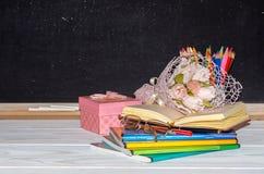 Blumen und Geschenk; Schreibhefte auf dem Schreibtisch des Lehrers Stockfoto
