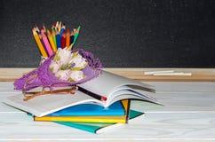 Blumen und Geschenk; Schreibhefte auf dem Schreibtisch des Lehrers Stockfotos