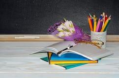 Blumen und Geschenk; Schreibhefte auf dem Schreibtisch des Lehrers Lizenzfreie Stockbilder