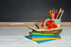 Blumen und Geschenk; Schreibhefte auf dem Schreibtisch des Lehrers Stockbild