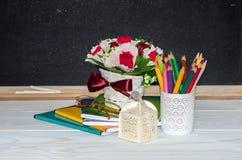 Blumen und Geschenk, Schreibhefte auf dem Schreibtisch des Lehrers Lizenzfreie Stockbilder