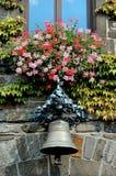 Blumen und Glocke über Eingang zu Rathaus in einem deutschen Dorf Stockfoto