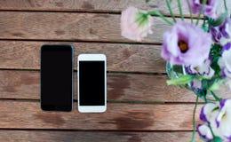 Blumen und intelligente Telefone auf der hölzernen Tabelle Stockfotos