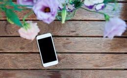 Blumen und intelligentes Telefon auf der hölzernen Tabelle Lizenzfreie Stockbilder