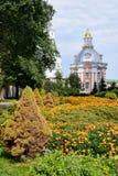 Blumen und kleine Smolenskaya-Kirche aufgrund Lavra - S Stockfotos
