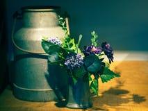 Blumen und Milch-Dosendekoration lizenzfreies stockfoto