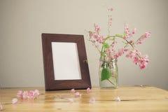 Blumen und weißer Fotorahmen auf Holztisch Lizenzfreie Stockbilder